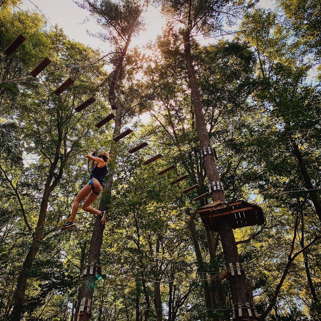弗兰肯穆斯空中公园的一名妇女在树上滑行