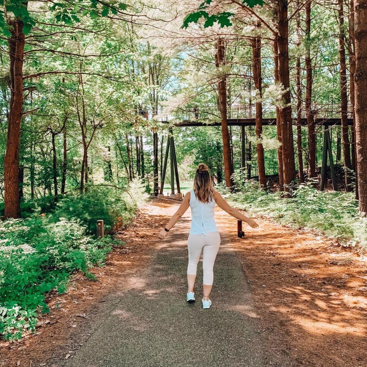 戴着健身器材的女孩在陶氏花园的怀廷森林林荫道散步