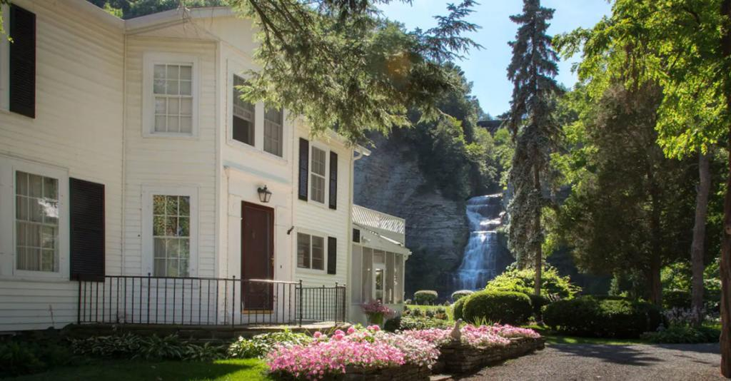 The Estate at Glenora Falls - Building Exterior with Waterfall
