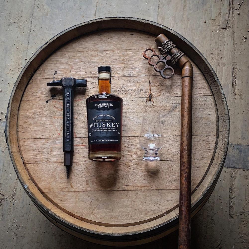 Bottle of Real Spirits Distilling Whiskey with glass and tools