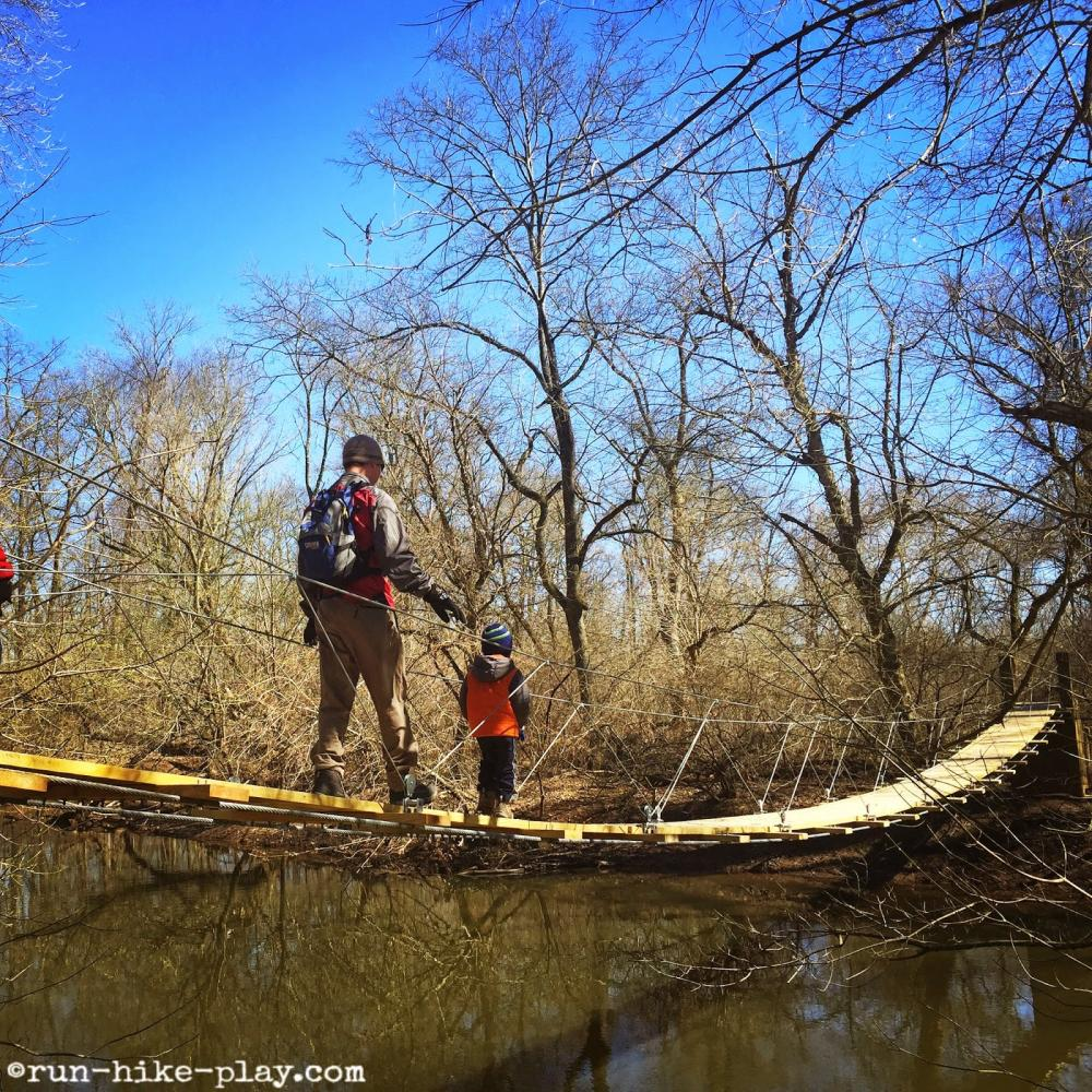 An adult and a child crossing over a rope bridge in Princeton Institute Woods