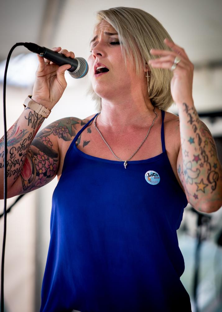 Woman with tattoos in a blue shirt with a LoCo sticker singing into a mic at 868 Estate Vineyards