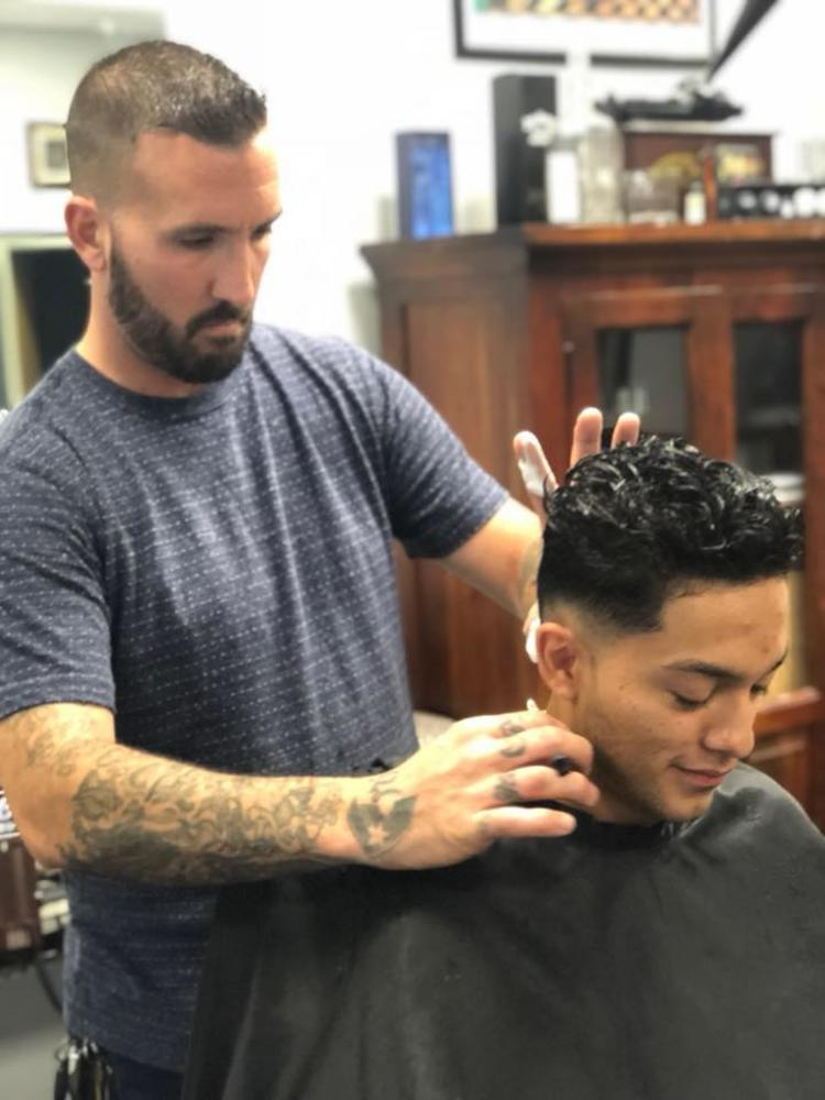 One man cuts another man's hair as he sits in a chair