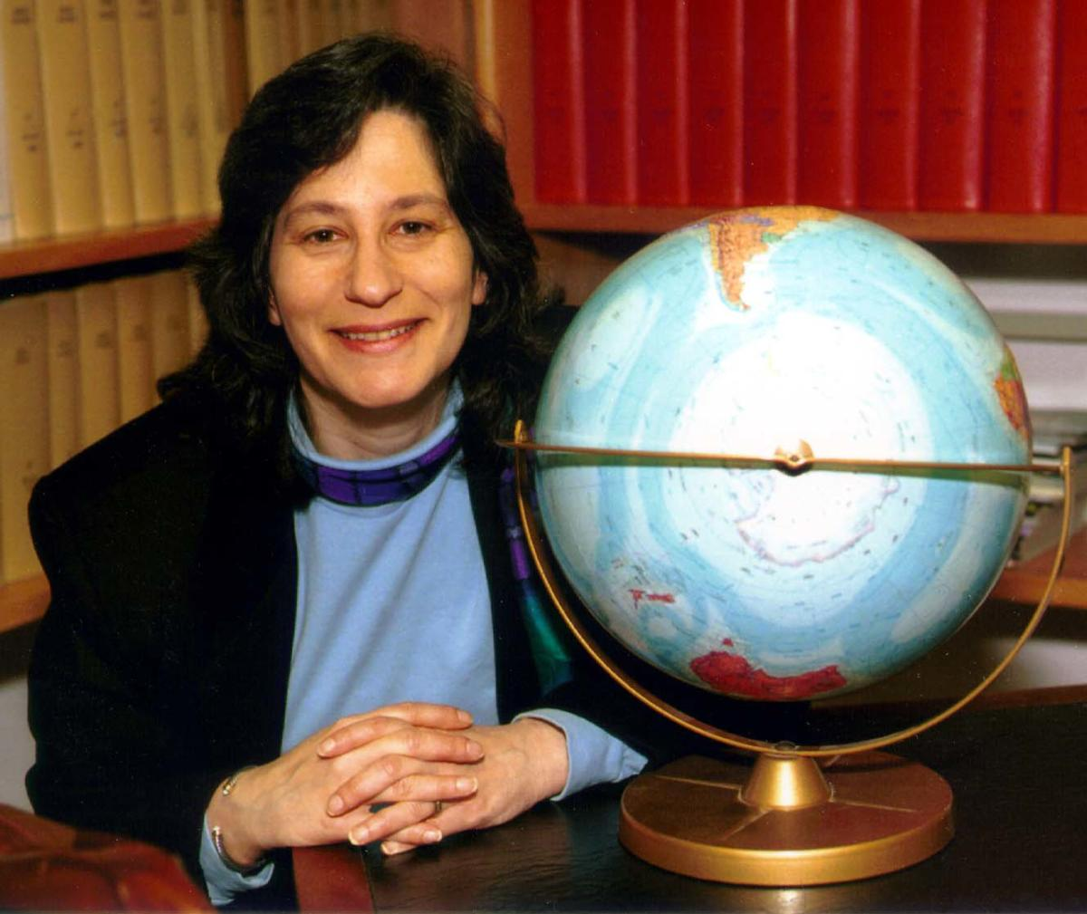 Head shot of Susan Solomon sitting next to a globe