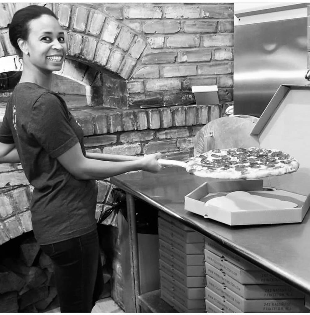 Smiling employee prepares a pepperoni pizza at Pizza Den