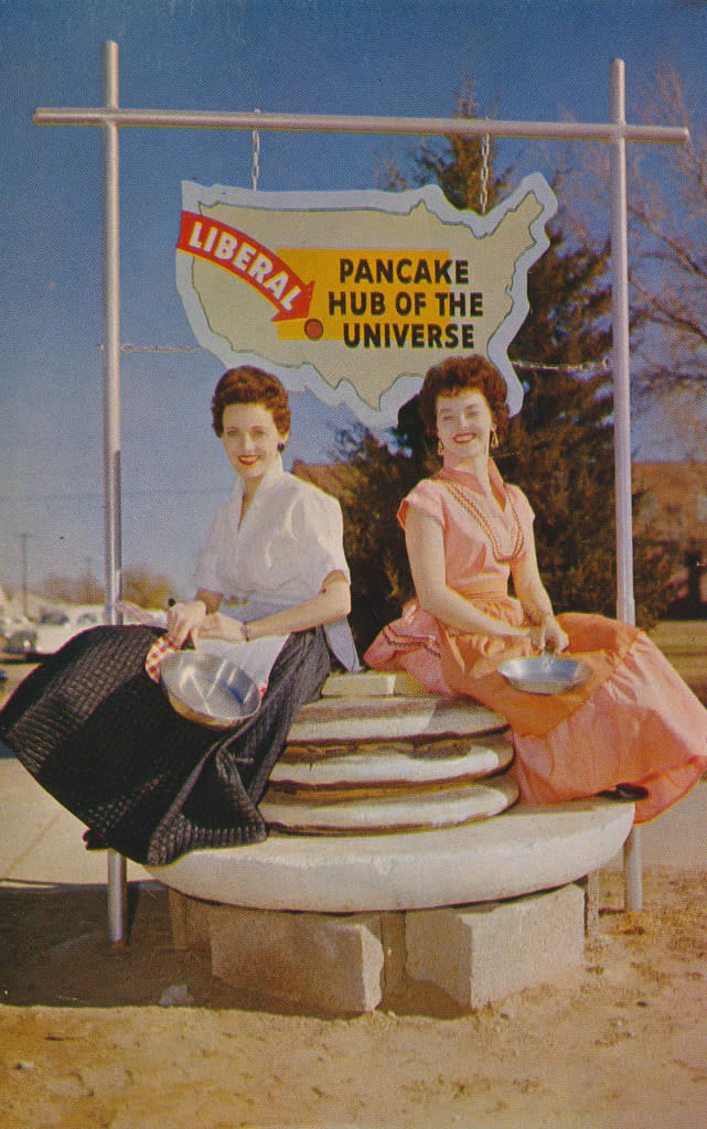 A vintage picture of 2 women sitting on a pancake statue at Pancake Race in Liberal, KS