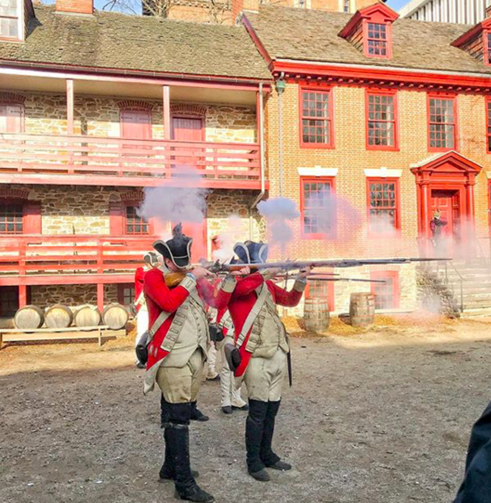 Redcoat reenactors firing their muskets at Old Barracks Museum in Princeton