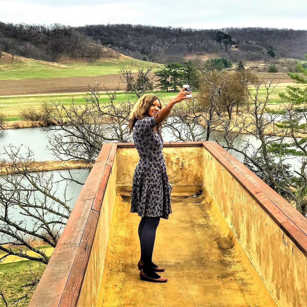 A woman standing on a walkway taking a selfie