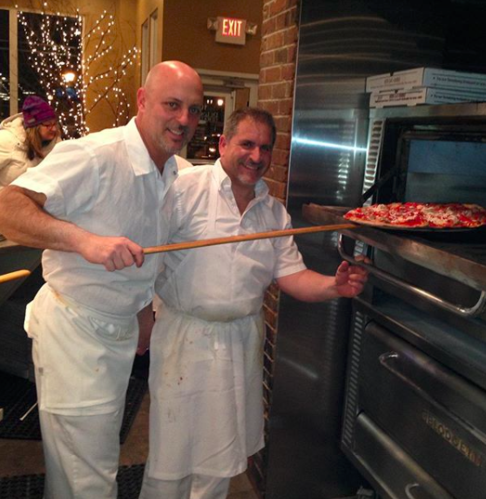 Two chefs sliding a pizza into an oven Delorenzo's in Princeton