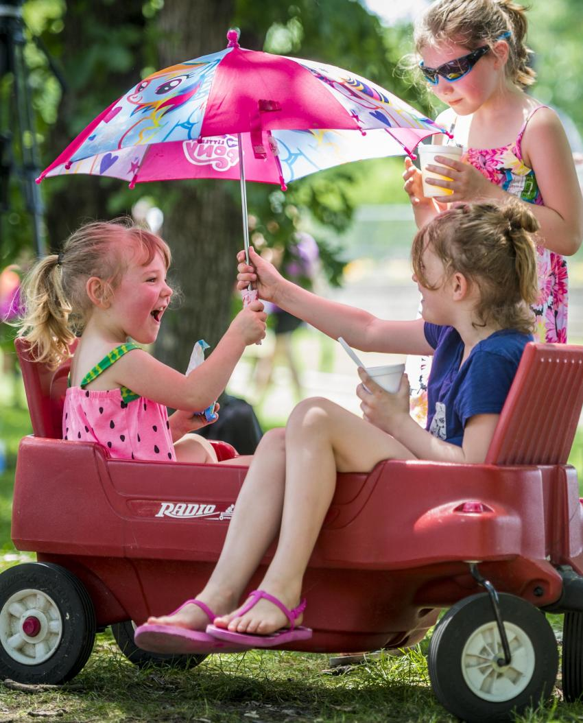 Two girls in a wagon, both holding an umbrella