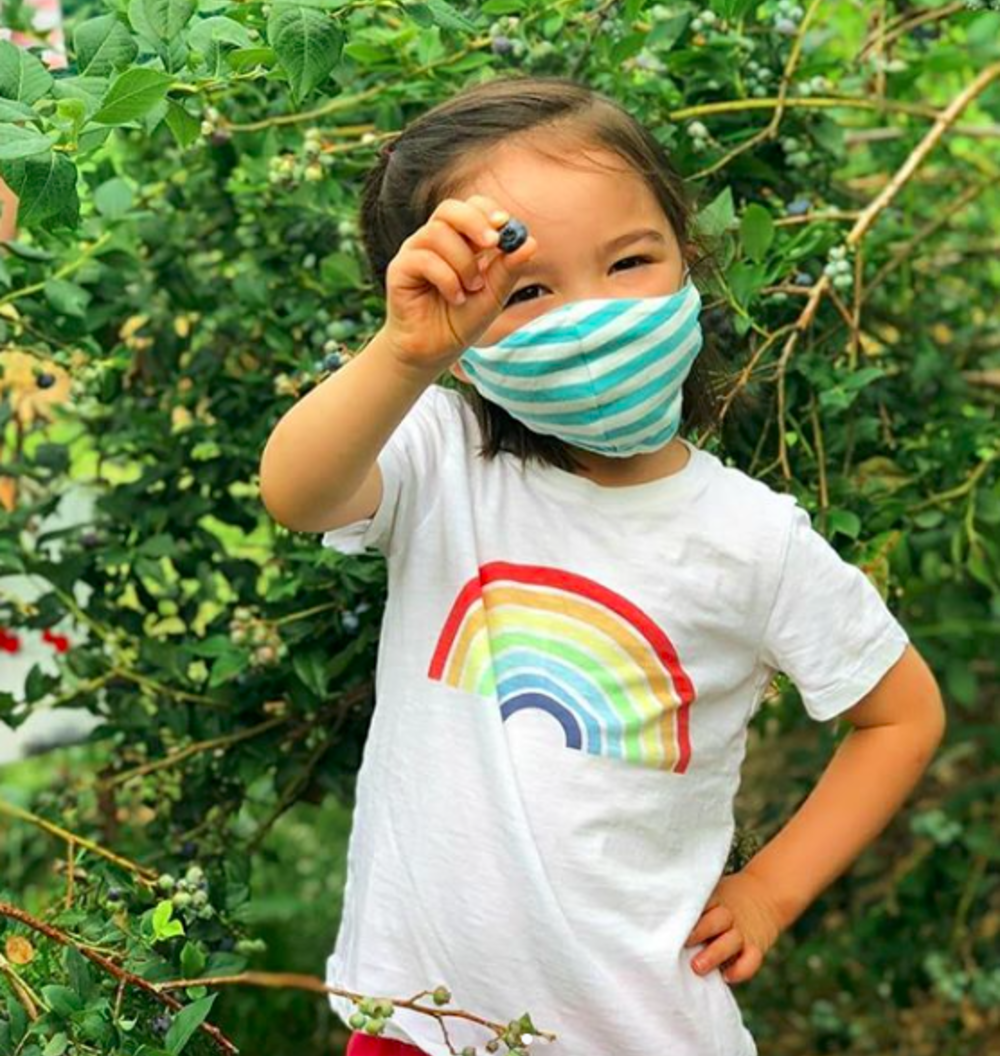 A masked child holding up a blueberry picked at Terhune Orchards near Princeton