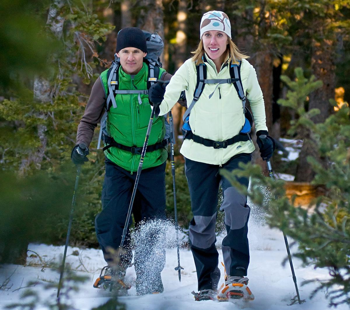 Man and woman snowshoeing among the pine trees in Boulder
