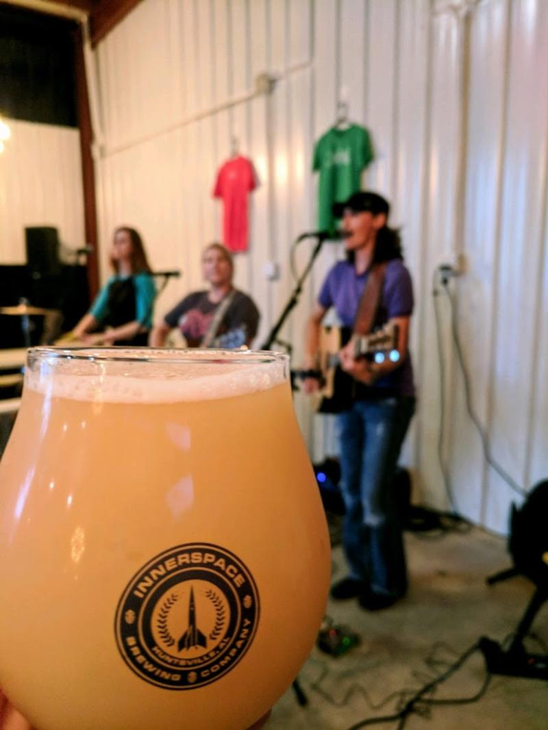 A beer held by a patron while watching a live band perform at Innerspace Brewing