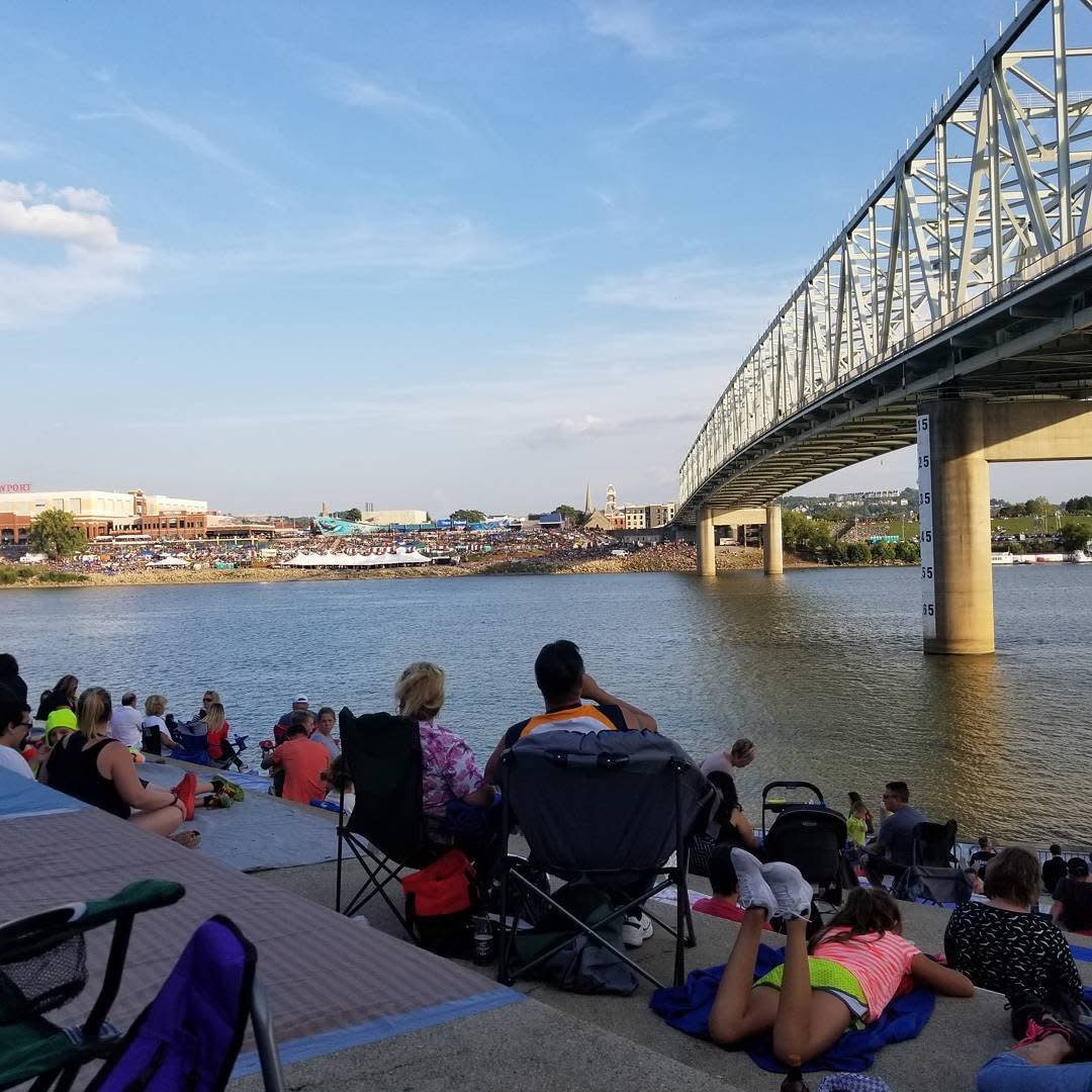 People sitting on serpentine wall in Cincinnati with the Ohio river and a bridge behind them
