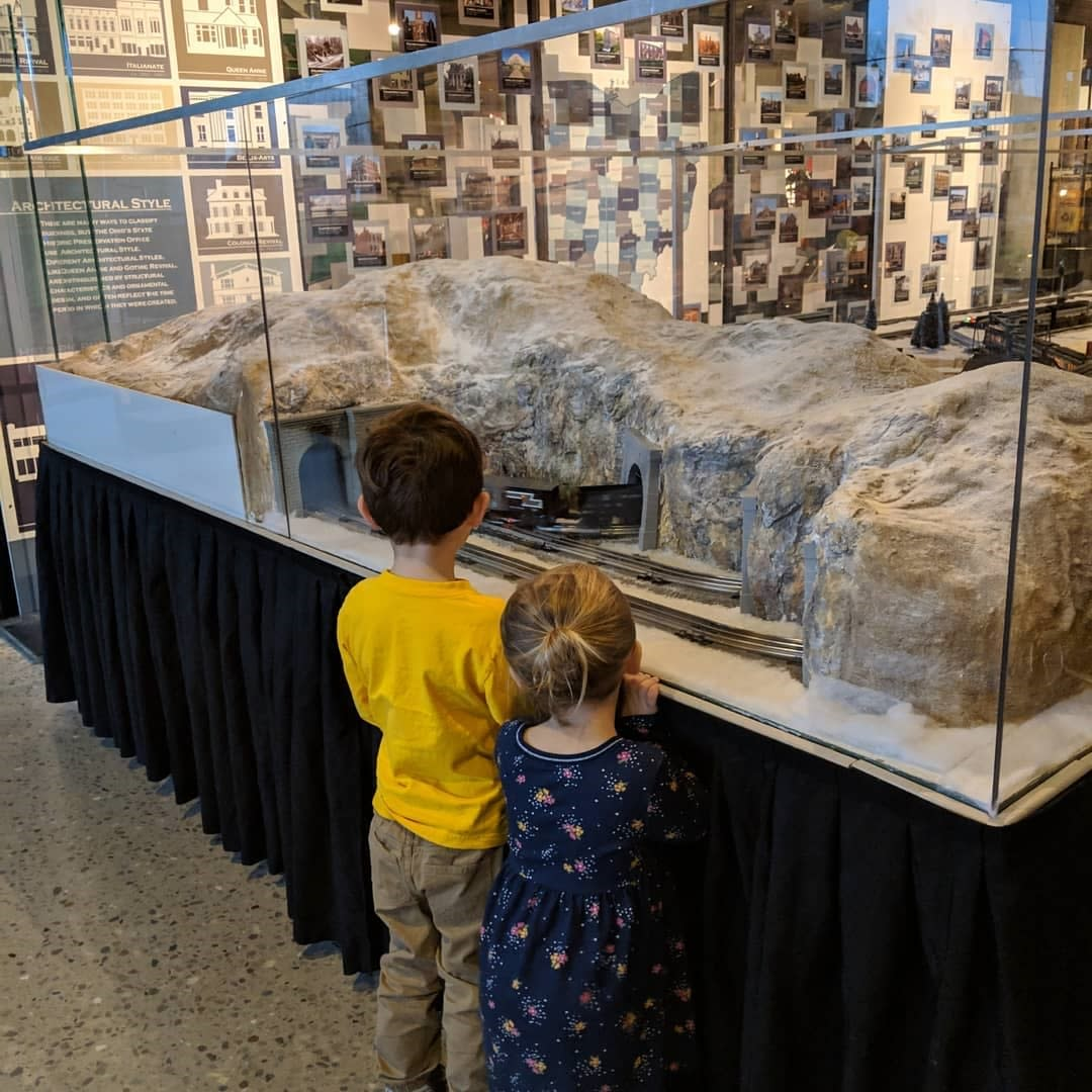 A young boy and girl looking through the glass at an exhibit at the Ohio History Center.