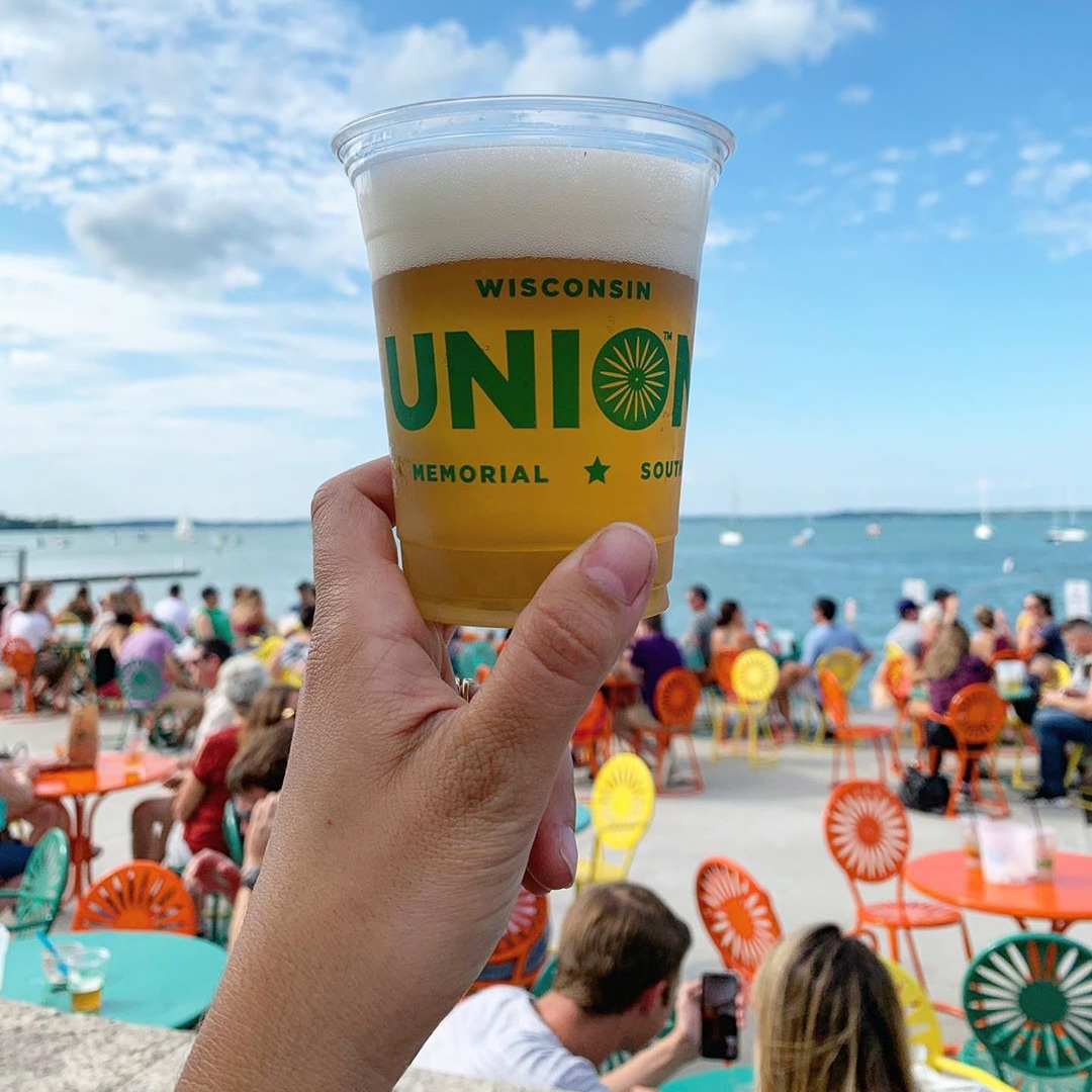 A person holds up a beer with the iconic Memorial Union Terrace chairs in the background
