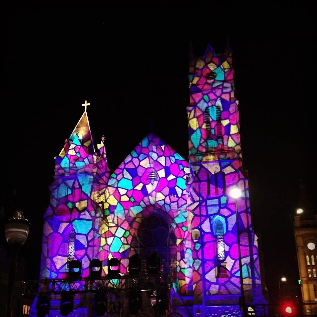 A church covered in stained glass light projections for BLINK Cincinnati