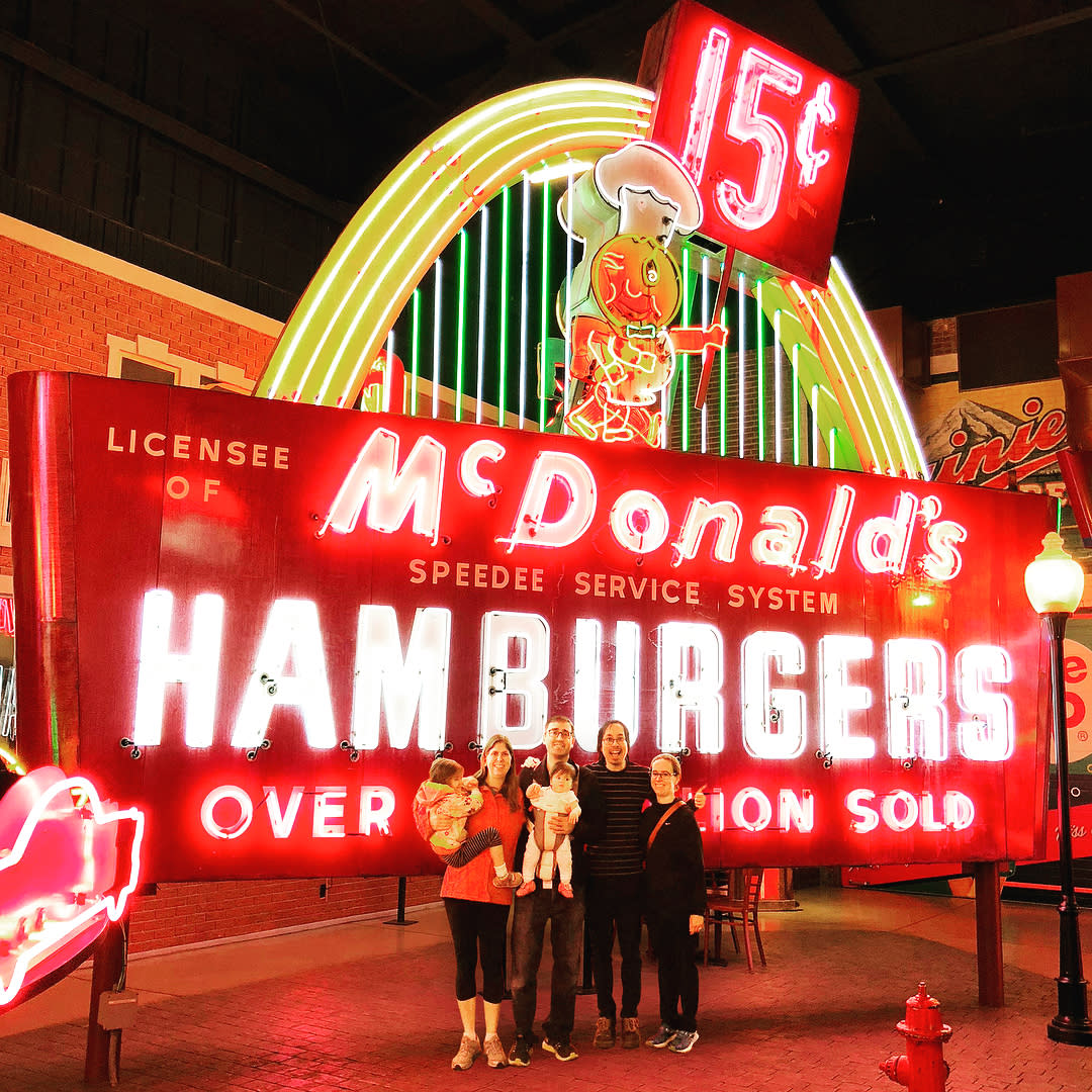 photo of family with kids touring the american sign museum in cincinnati ohio standing in front of a vintage mcdonalds hamburgers sign