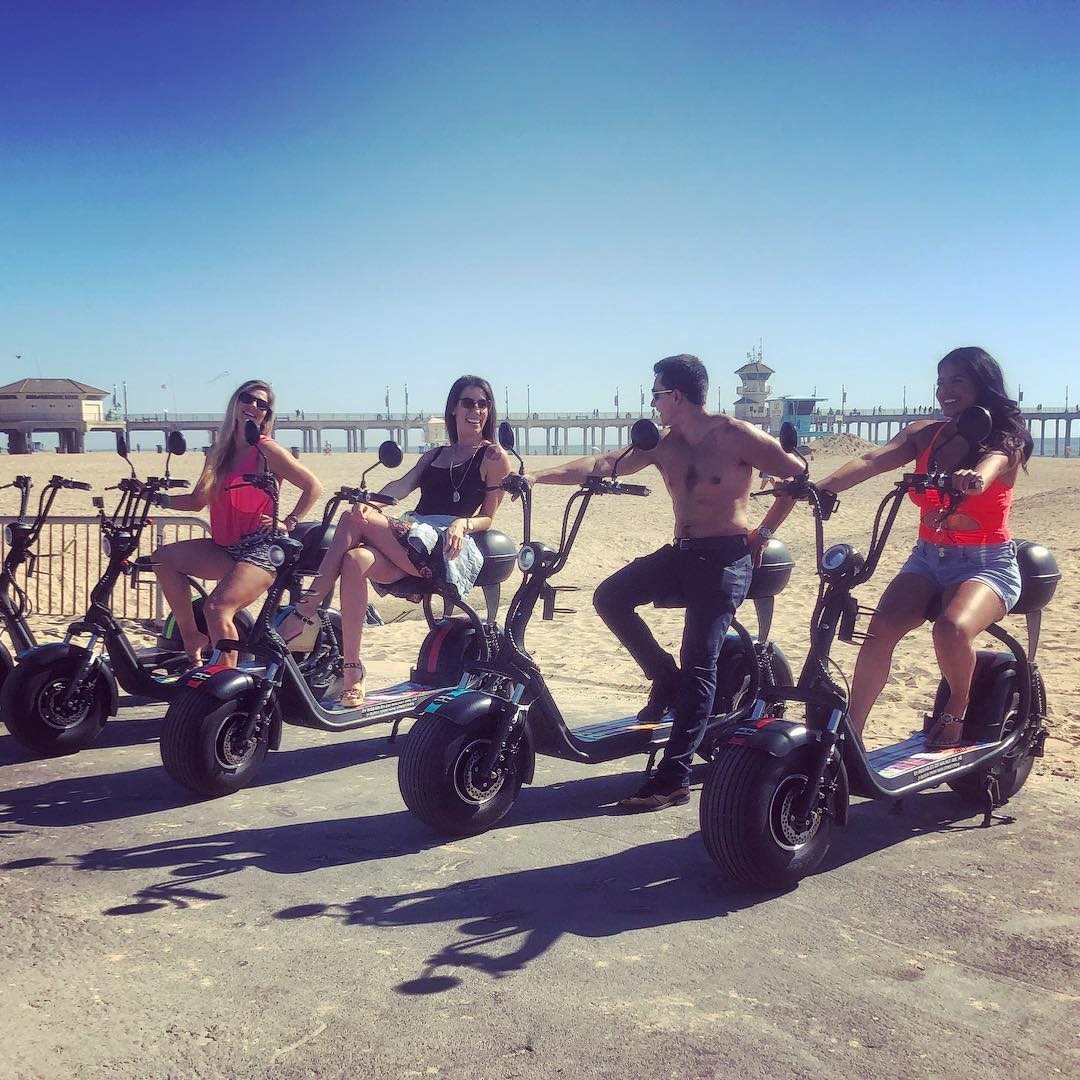 A group of friends sitting on scooters by the beach in Huntington Beach Biking
