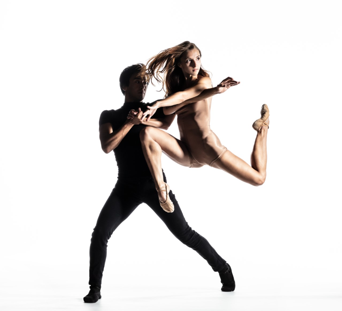 A man dancing with a woman that's in mid-air in front of a white background.