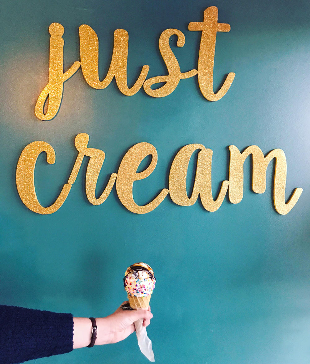 Hand holding ice cream cone at Just Cream Ice Cream Boutique in Fort Wayne