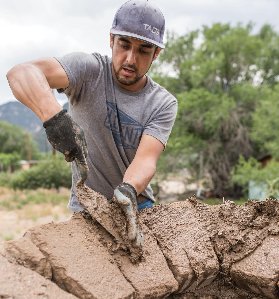 Volunteer Miguel Gonzales helps build Quesa's Farmers' Market horno