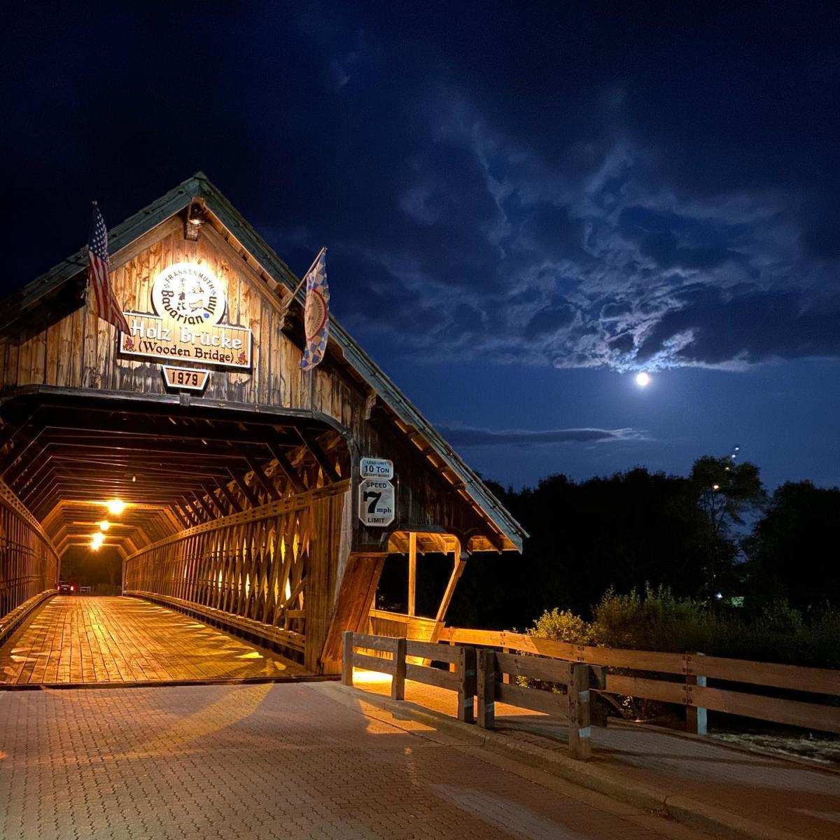 Frankenmuth Holz Brucke Wooden Covered Bridge illuminated against a dark night sky