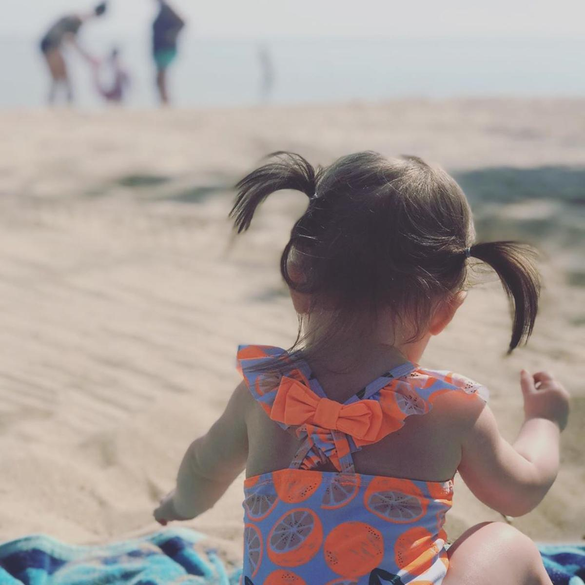 Little girl in a colorful swimsuit playing in the sand on the beachfront at Bay City State Park