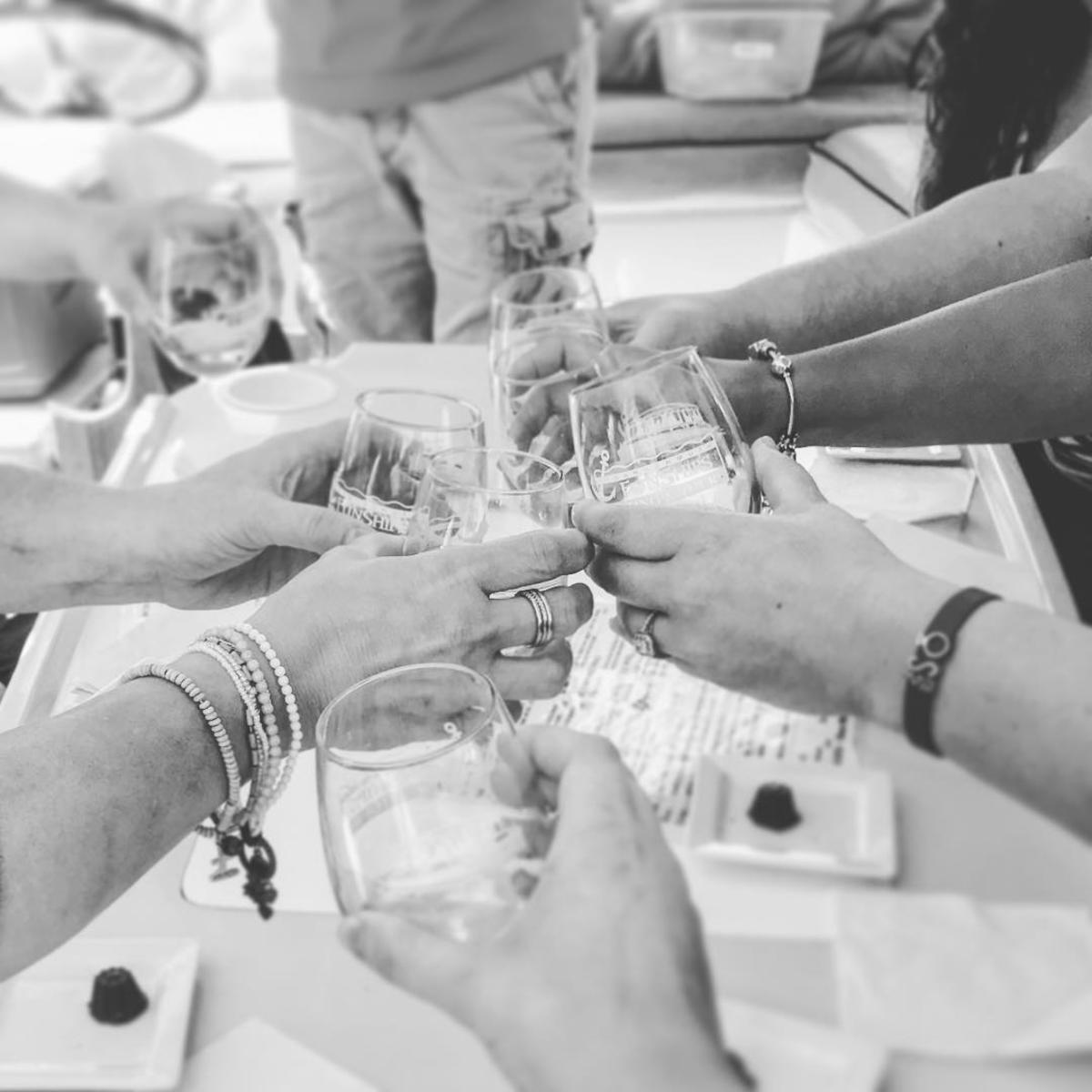 Friends toasting with their souvenir glasses on a Wine Tasting River Tour with Frankenmuth FunShips