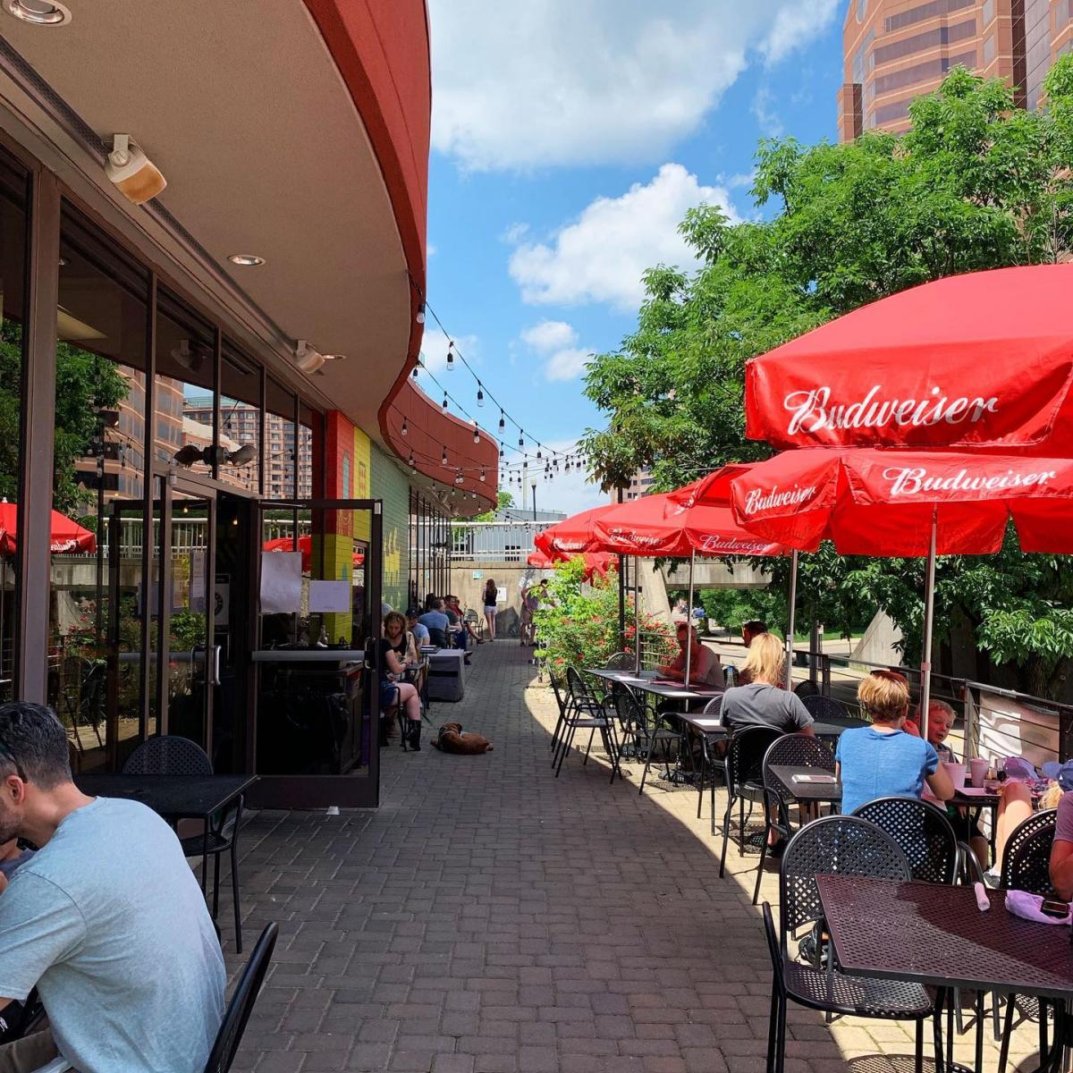 red umbrellas and black outdoor patio tables on a brick sidewalk in front of the gruff in covington ky
