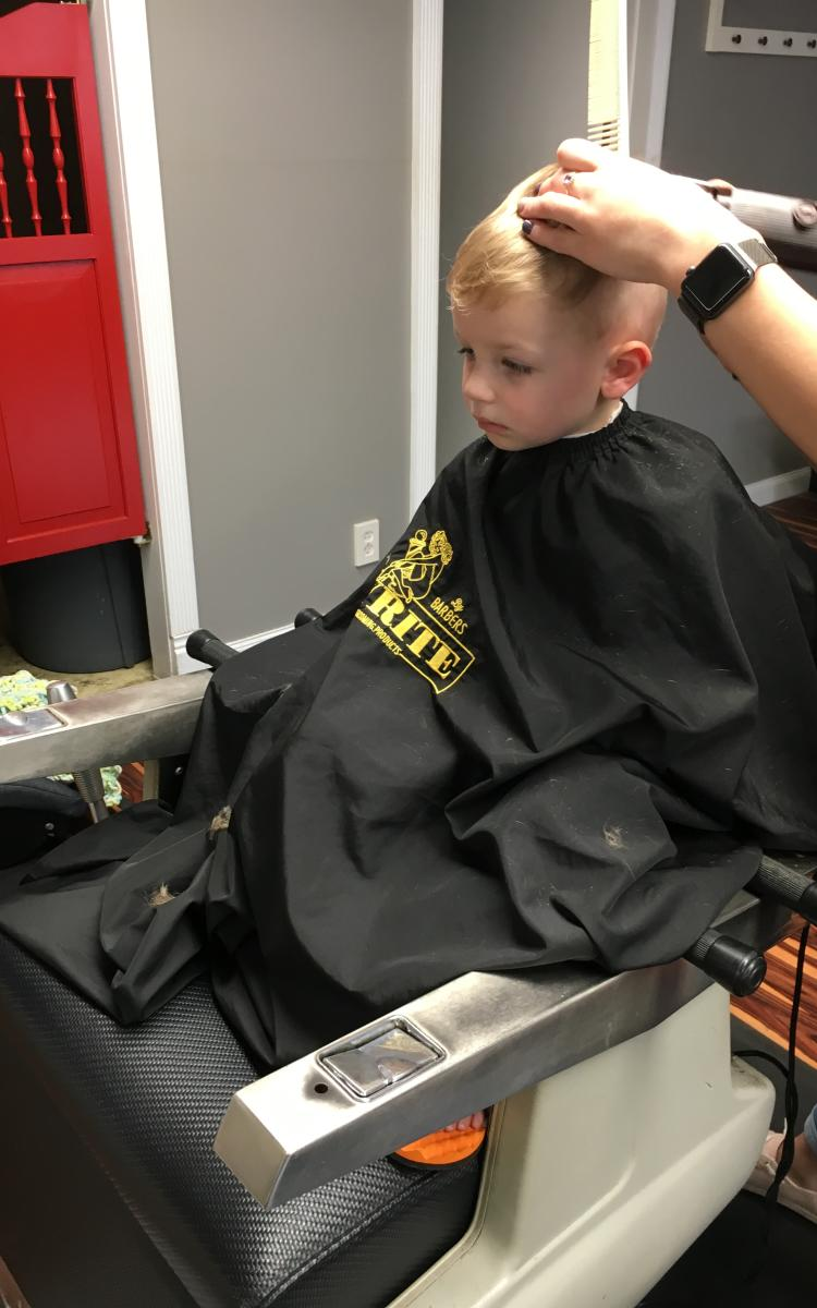 A young boy sits in a booster chair for a haircut