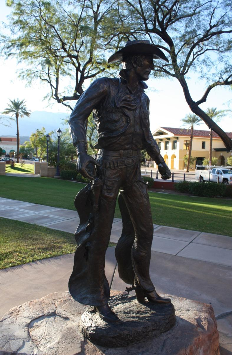 Bronze statue of a man wearing a cowboy hat