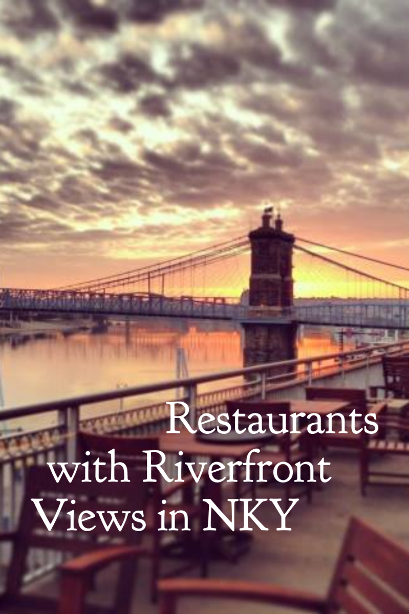 The Roebling suspension bridge at sunrise with a restaurant patio in the foreground and the title Restaurants with Riverfront Views in NKY