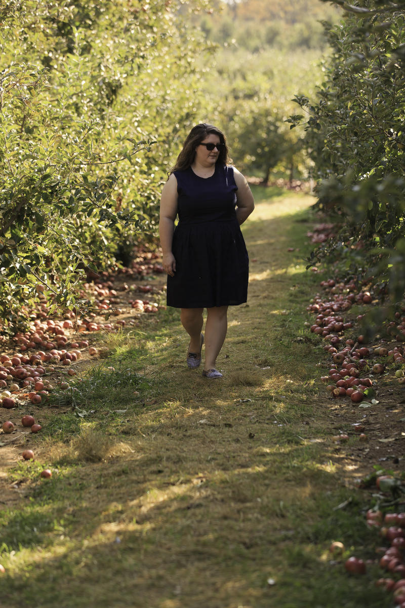 Woman strolling through apple trees at Larriland Farm
