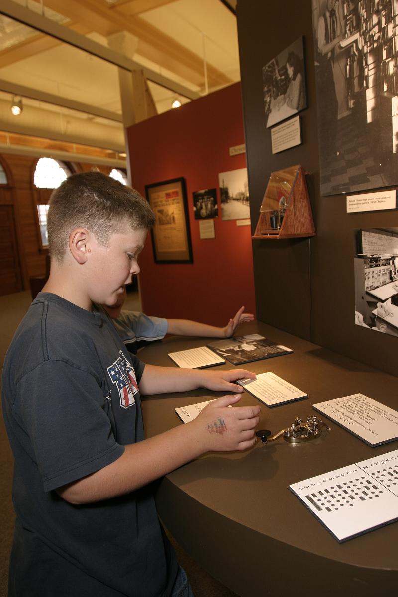 Young boys read a display and try out a telegraph machine at the Cheyenne Depot Museum