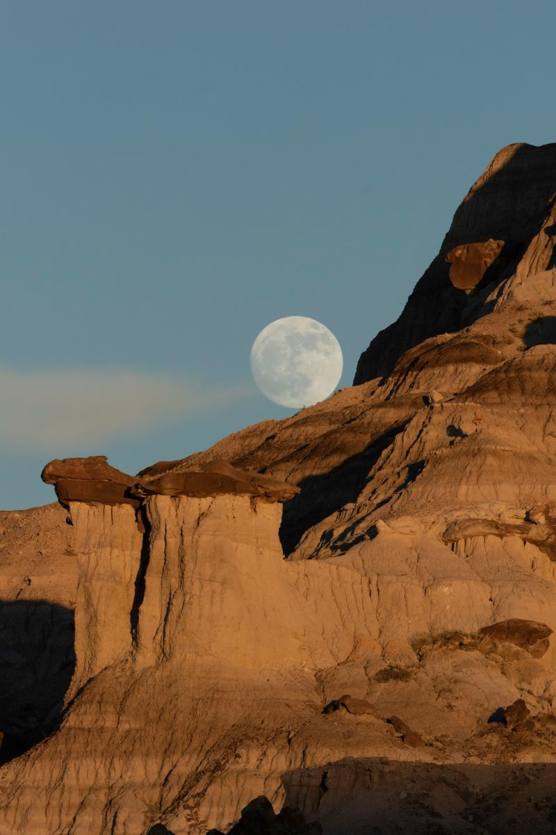 The moon poses above a barren cliff.