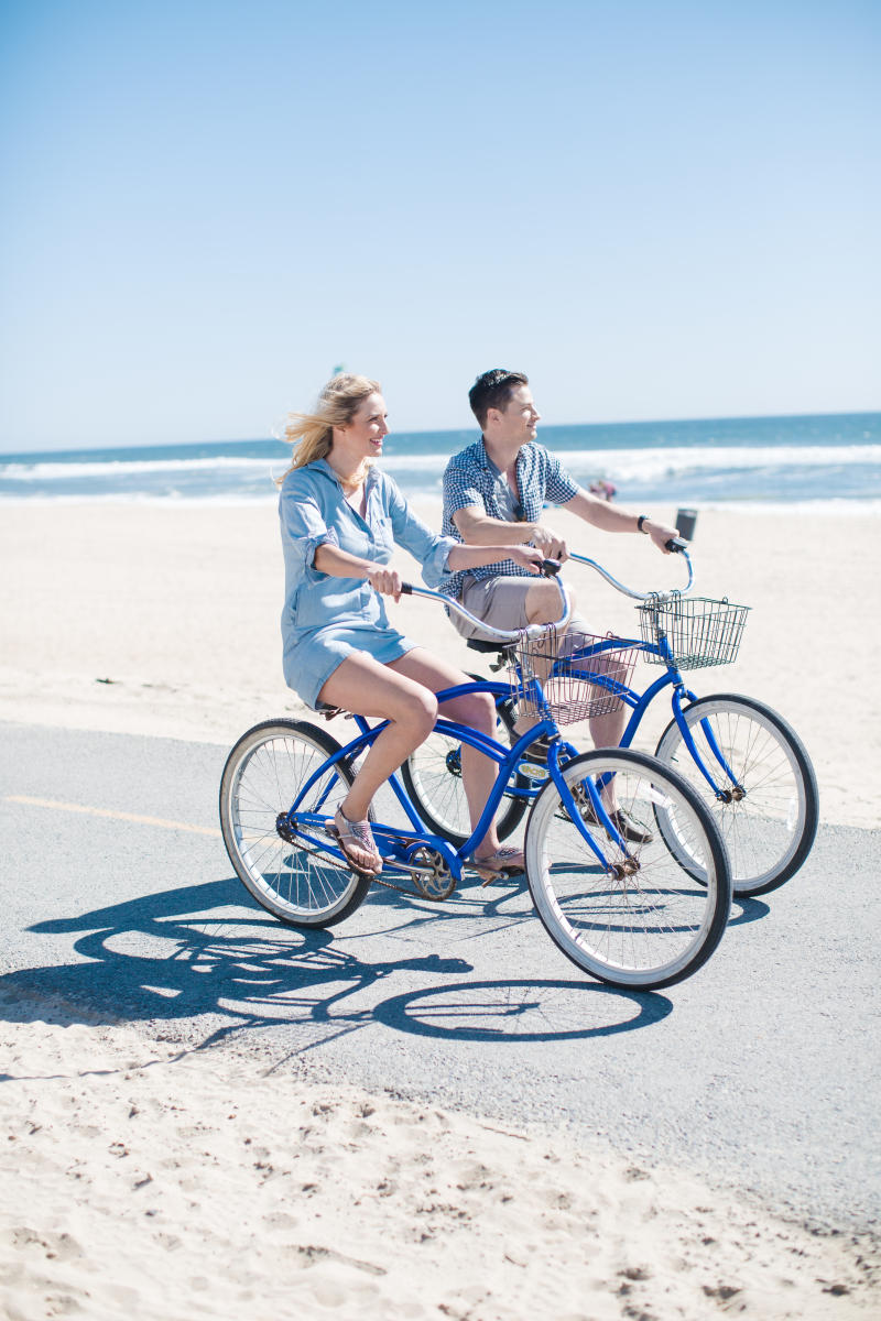Man and woman riding bikes side by side on a bike trail in Huntington Beach