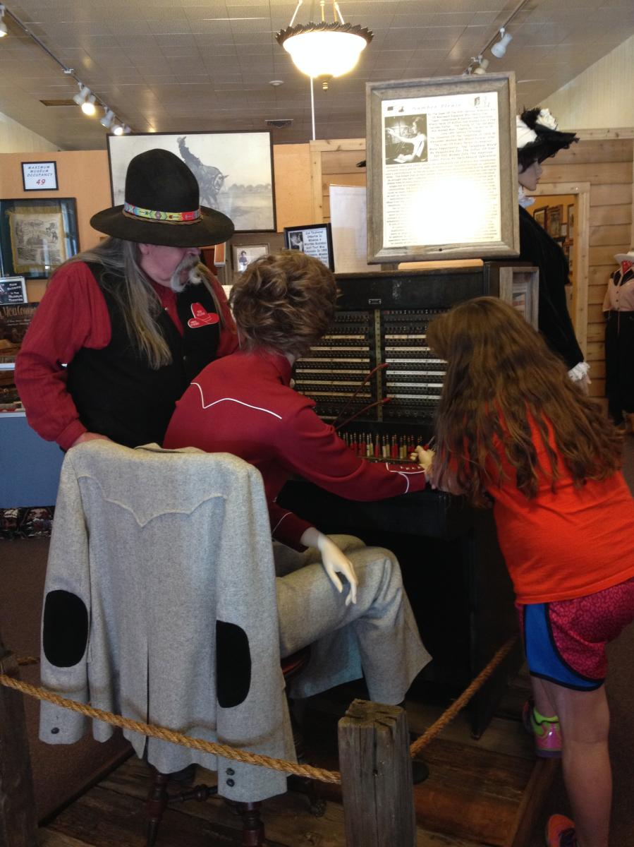 Western-dressed tour guide explains to young girl how operating boards worked with a museum display featuring a mannequin.