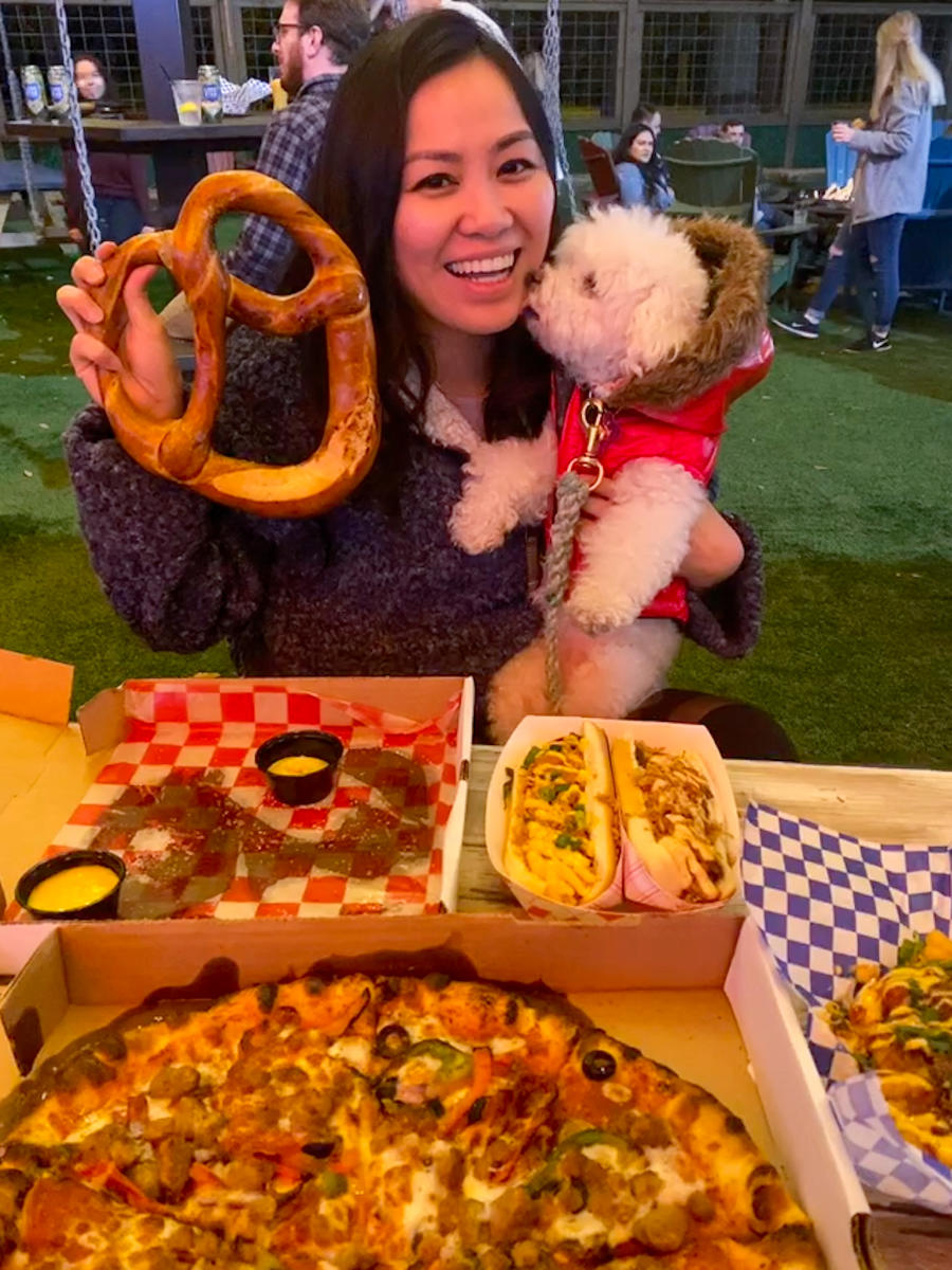 Women posing with dog while holding a pretzel at Little Woodrow