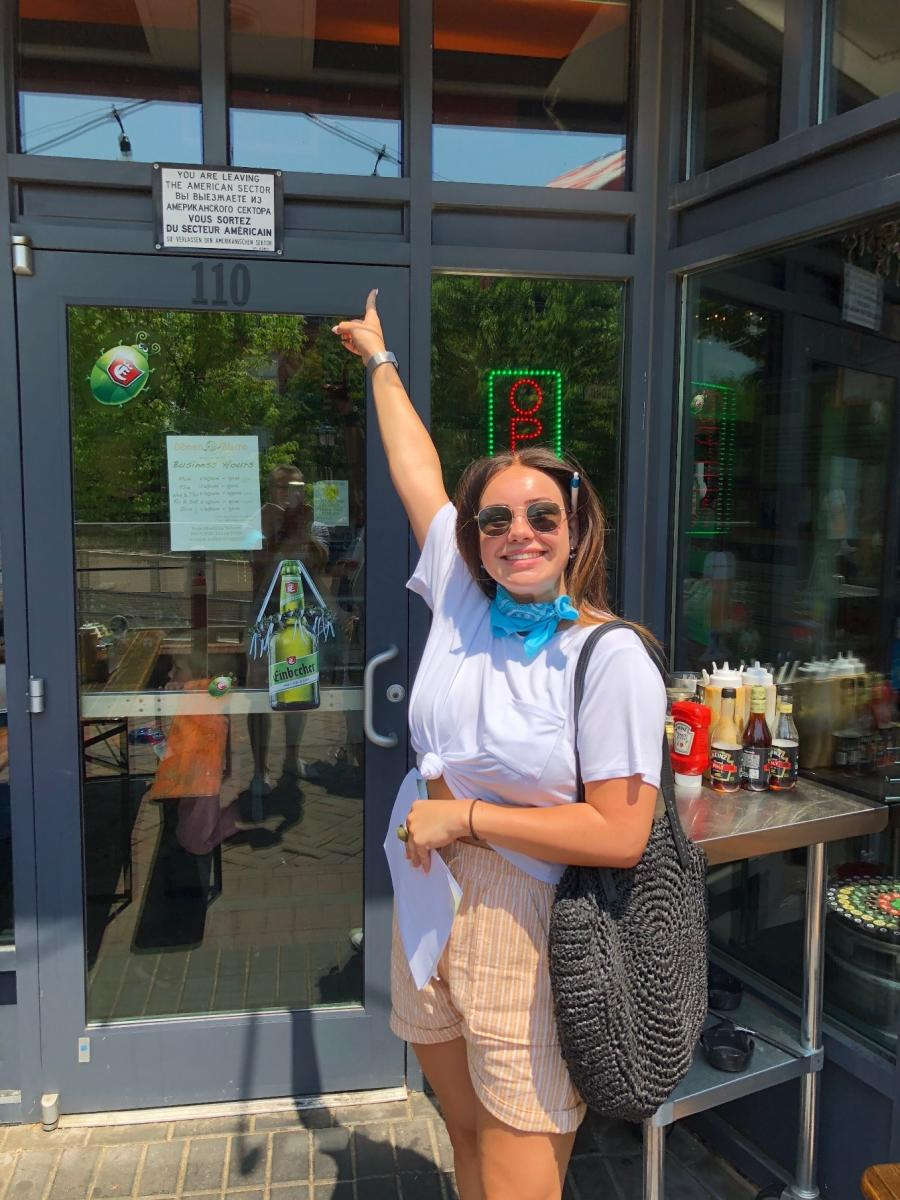 Woman pointing to the Doner Bistro sign