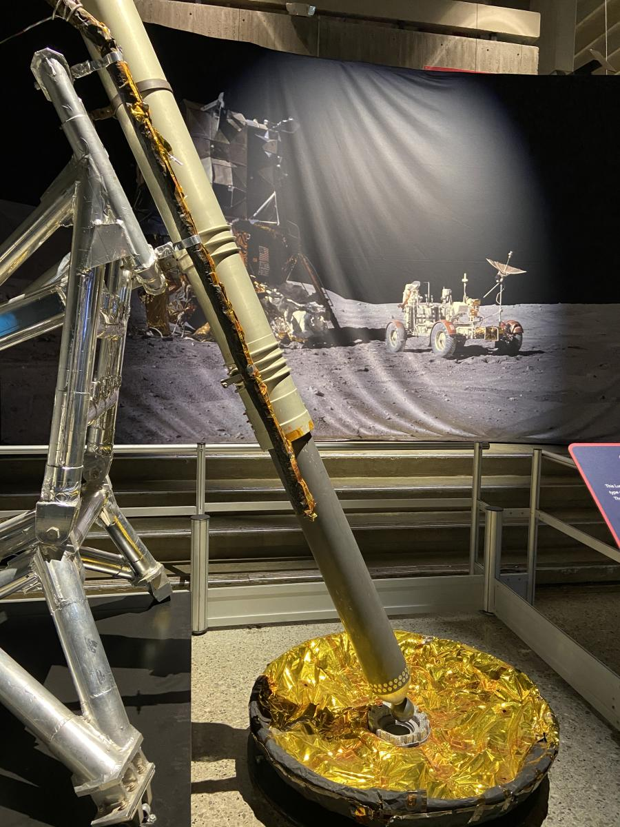 A lunar lander sits next to an image of the first lunar lander to touch down on the moon's surface.