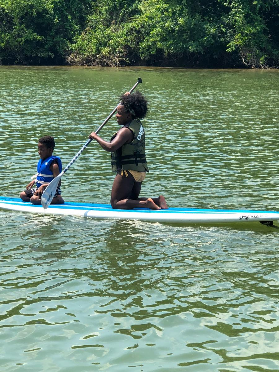 Zenovia Paddleboarding Woman With Child On Paddleboard