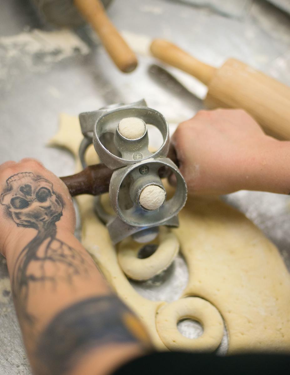 Punching through dough at Rebel Doughnuts