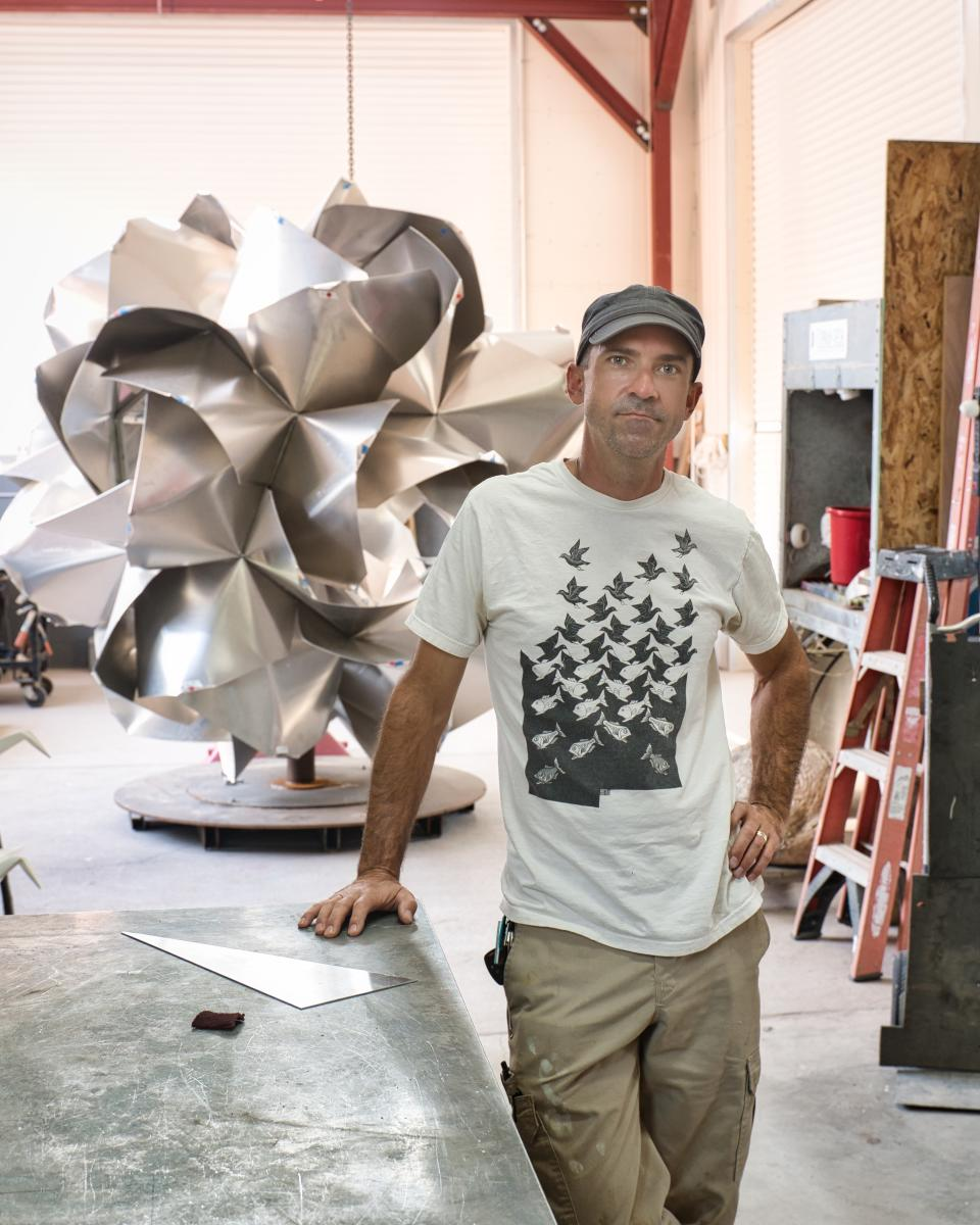 Kevin Box in his studio with Scents of Sincerity, an in-progress aluminum rose, New Mexico Magazine