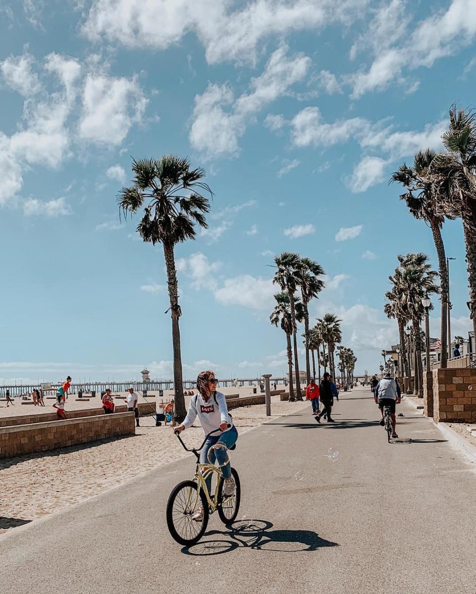 A woman biking on a trail near the beach in Huntington Beach
