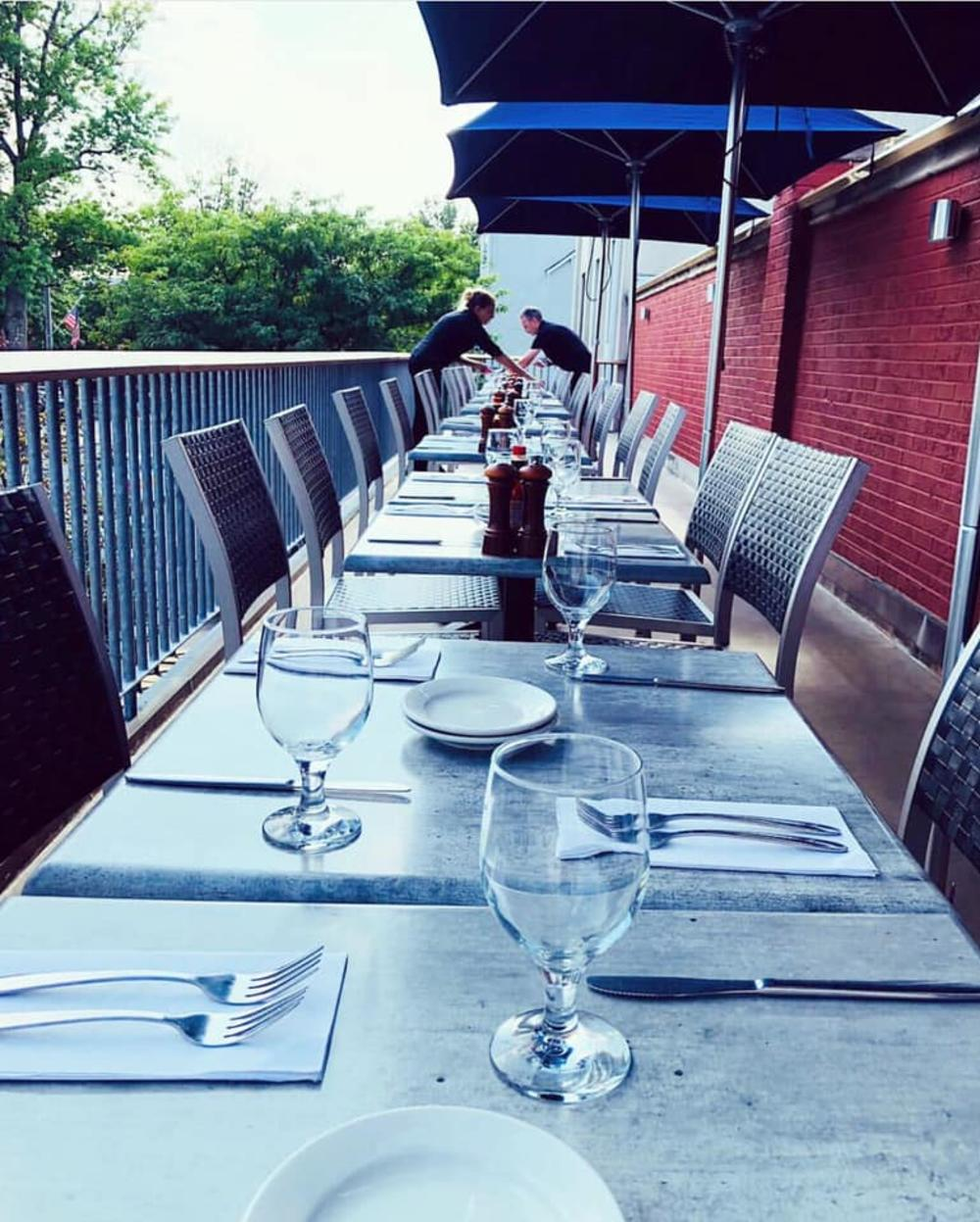 A line of tables set for dinner at a restaurant outside