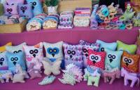 Handmade crafts, including brightly-colored animal-shaped pillows and stuffed animals, sit on a table on display for purchase