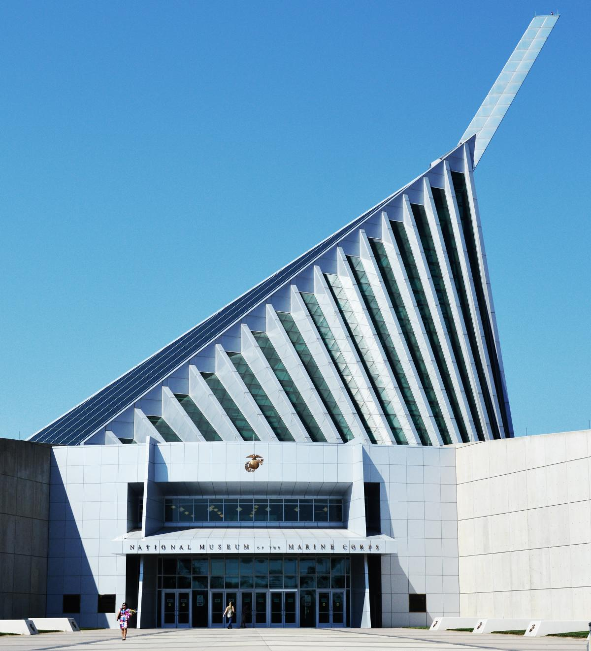 A white building with an off-center triangle roof