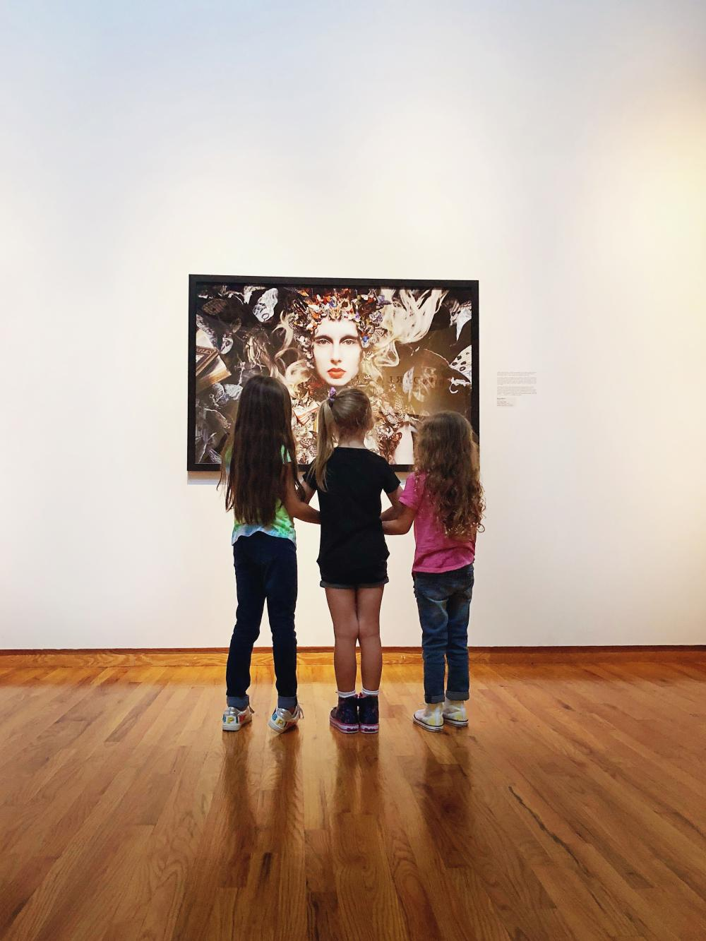 Three young girls browsing photography at the Fort Wayne Museum of Art