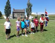 Children practice military drills at Fort Ontario State Historic Site in a unique program coordinated by Oswego County AmeriCorps members Ian Mumpton (right) and Steven Woods.